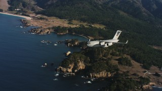 WAAF05_C046_011850 - 4K stock footage aerial video of a Boeing C-17 flying away from the coast of Northern California