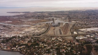 WAAF05_C069_0118C8 - 4K stock footage aerial video of following a Boeing C-17 flying over industrial buildings in Northern California