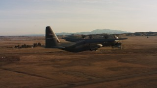 WAAF06_C002_0119TW - 4K stock footage aerial video of a Lockheed Martin C-130J lifting off from Travis Air Force Base at sunset, California