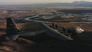 WAAF06_C003_01192T - 4K stock footage aerial video of a Lockheed Martin C-130J flying near marshland at sunset in Northern California