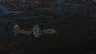 WAAF06_C006_0119G1 - 4K stock footage aerial video of a Lockheed Martin C-130J flying over wetlands at twilight in Northern California