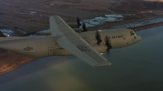 WAAF06_C007_0119WJ - 4K stock footage aerial video of revealing a Lockheed Martin C-130J flying over wetlands in Northern California, sunset