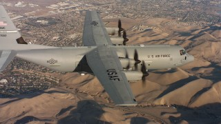 WAAF06_C010_0119DW - 4K stock footage aerial video of a Lockheed Martin C-130J flying near neighborhoods at sunset in Northern California