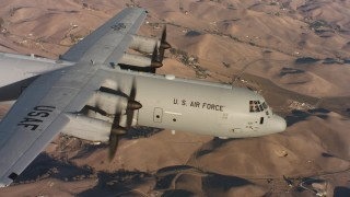 WAAF06_C013_0119HX - 4K stock footage aerial video of a Lockheed Martin C-130J in flight over brown hills at sunset, Northern California