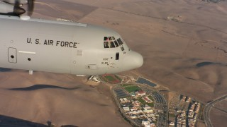 WAAF06_C014_01194G - 4K stock footage aerial video of the nose and cockpit section of a Lockheed Martin C-130J flying at sunset in Northern California
