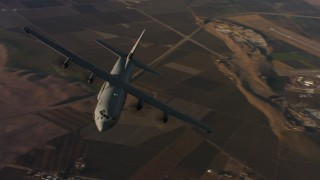 WAAF06_C026_0119G8 - 4K stock footage aerial video of flying around the front end of a Lockheed Martin C-130J at sunset, Northern California