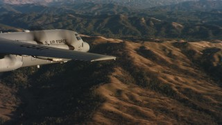 WAAF06_C028_0119QR - 4K stock footage aerial video of revealing a Lockheed Martin C-130J flying over mountains at sunset in Northern California