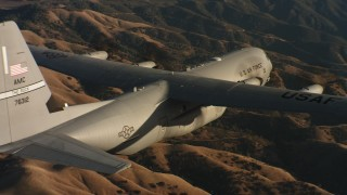 WAAF06_C029_0119C1 - 4K stock footage aerial video of a Lockheed Martin C-130J flying over rolling hills at sunset in Northern California