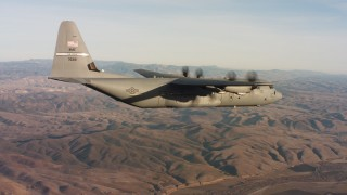 WAAF06_C033_0119HP - 4K stock footage aerial video of a Lockheed Martin C-130J flying high over hills at sunset in Northern California