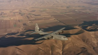 WAAF06_C036_0119QH - 4K stock footage aerial video of a Lockheed Martin C-130J flying over hills and farms at sunset in Northern California
