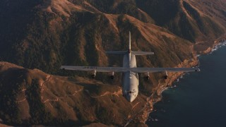 WAAF06_C052_0119WK - 4K stock footage aerial video reverse view of a Lockheed Martin C-130J flying over mountains near coast of Northern California