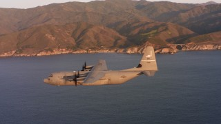 WAAF06_C059_0119W4 - 4K stock footage aerial video of a Lockheed Martin C-130J flying over the ocean at sunset near coast of Northern California