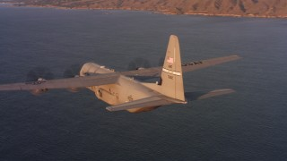 WAAF06_C059_0119W4_S000 - 4K stock footage aerial video of flying around a Lockheed Martin C-130J near the coast of Northern California at sunset