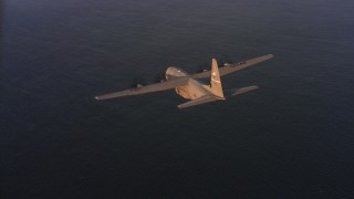 WAAF06_C061_0119SS - 4K stock footage aerial video fly around a Lockheed Martin C-130J over the ocean at sunset in Northern California