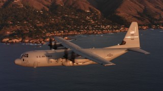 WAAF06_C062_0119BD - 4K stock footage aerial video of a Lockheed Martin C-130J in flight over the ocean near the coast at sunset, Northern California