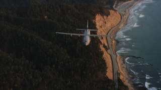 WAAF06_C072_01194X - 4K stock footage aerial video of a Lockheed Martin C-130J following the coast at sunset in Northern California