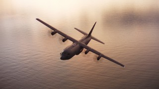 WAAF06_C086_011941 - 4K stock footage aerial video of a Lockheed Martin C-130J over San Francisco Bay at sunset, California