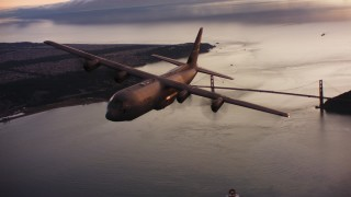 WAAF06_C087_0119KX - 4K stock footage aerial video of a Lockheed Martin C-130J flying over the Golden Gate Bridge at sunset, California