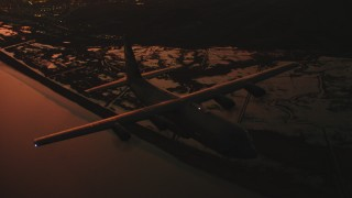 WAAF06_C090_01191R - 4K stock footage aerial video fly around front of Lockheed Martin C-130J over wetlands at sunset, Northern California