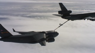 WAAF07_C051_0119AJ - 4K stock footage aerial video of a McDonnell Douglas KC-10 fueling a Boeing C-17 above clouds in Northern California