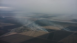 WAAF07_C081_0119BK - 4K stock footage aerial video of smoke rising from farm fields in Northern California