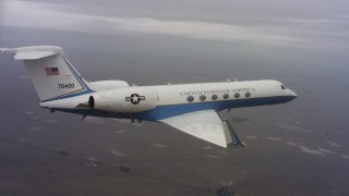 WAAF08_C037_0119GC - 4K stock footage aerial video of a Gulfstream C-37A flying over farmland in Northern California