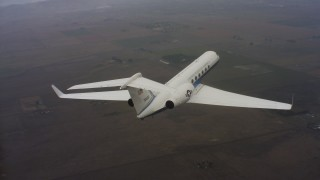 WAAF08_C039_0119FF - 4K stock footage aerial video of a Gulfstream C-37A flying high above farm fields in Northern California