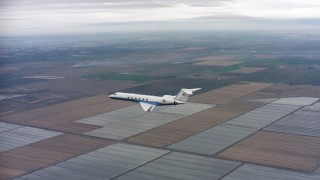 WAAF08_C056_0120GH - 4K stock footage aerial video of a Gulfstream C-37A flying over covered fields in Northern California
