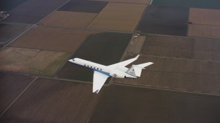 WAAF08_C058_0120H6 - 4K stock footage aerial video of a Gulfstream C-37A as it flies over fields in Northern California
