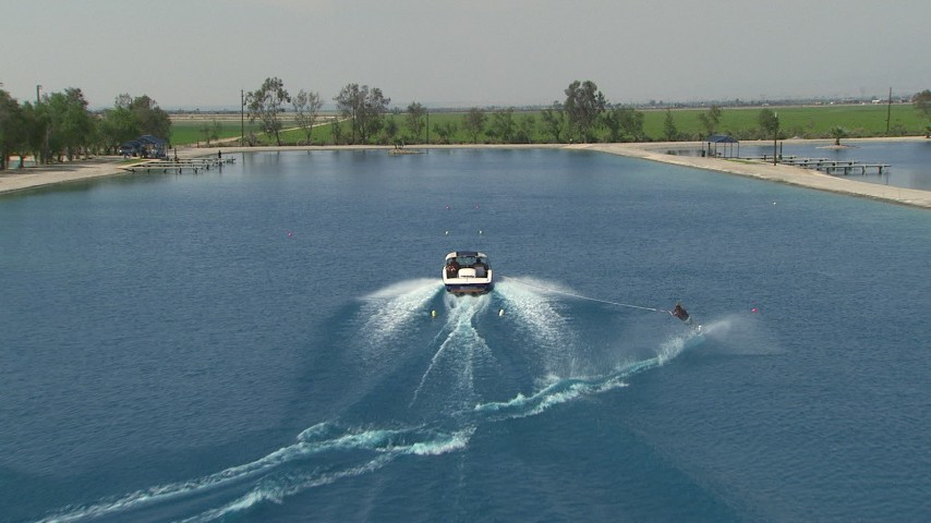 HD stock footage aerial video track woman waterskiing on a lakeCentral Valley, California Aerial Stock Footage | AF0001_000022
