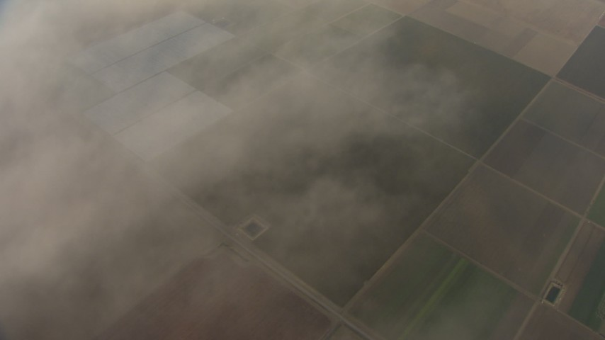 HD stock footage aerial video of flying through clouds, revealing farmland below, Central Valley, California Aerial Stock Footage | AF0001_000027