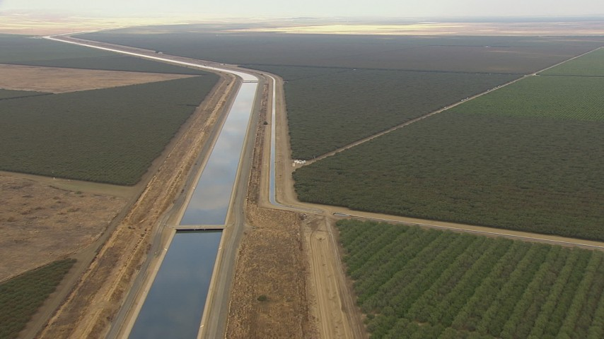 HD stock footage aerial video follow California Aqueduct winding through farmland and tilt to a bird's eye view, Central Valley, California Aerial Stock Footage | AF0001_000035