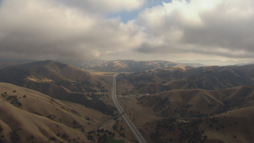 HD stock footage aerial video follow Interstate 5 through Tejon Pass, California, with low clouds overhead Aerial Stock Footage | AF0001_000041