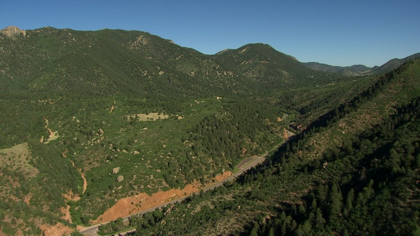 HD stock footage aerial video of flying over green slopes to reveal a road in the Rocky Mountains, Colorado Aerial Stock Footage | AF0001_000079
