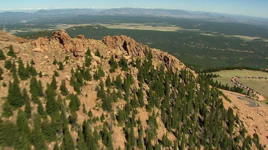 HD stock footage aerial video fly over jagged slope of Pikes Peak, and tilt to road winding up the mountain, Colorado Aerial Stock Footage | AF0001_000089