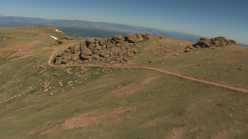 HD stock footage aerial video pan across the summit and fly over a hiking trail, patches of snow, Pikes Peak, Colorado Aerial Stock Footage | AF0001_000094