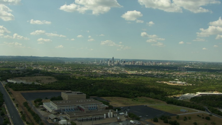 HD stock footage aerial video of the skyline of Downtown Austin, Texas seen while flying over a manufacturing plant Aerial Stock Footage | AF0001_000099