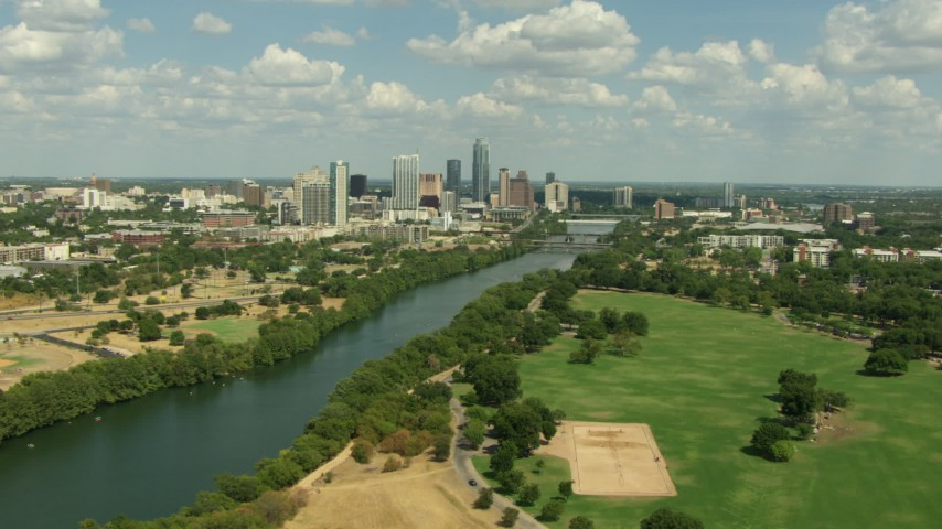 Fly over Austin City Limits Music Festival grounds to approach the lake and Downtown Austin, Texas Aerial Stock Footage | AF0001_000106