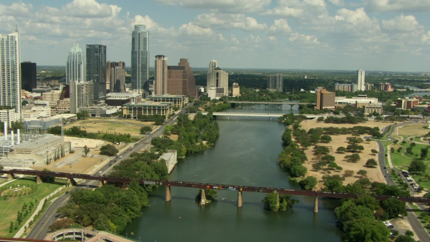 Follow Lady Bird Lake over the 1st Street Bridge, tilt to cars crossing Congress Avenue Bridge, Downtown Austin, Texas Aerial Stock Footage | AF0001_000107