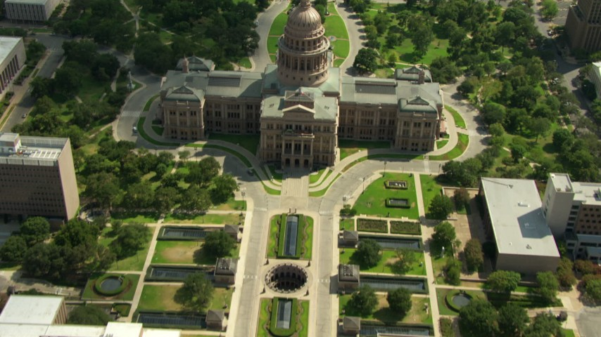 Bird's eye view of University of Texas and streets leading to reveal of Texas State Capitol, Downtown Austin, Texas Aerial Stock Footage | AF0001_000113