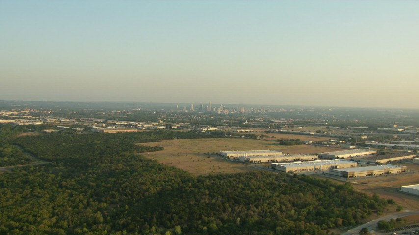 Flyby warehouse buildings to approach the skyline of Downtown Austin, Texas Aerial Stock Footage | AF0001_000126