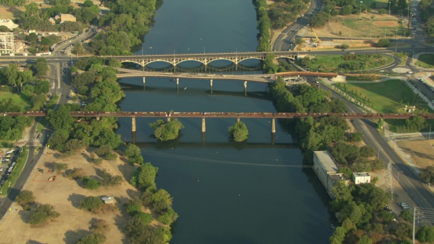 Reverse view of four bridges spanning Lady Bird Lake, Downtown Austin, Texas Aerial Stock Footage | AF0001_000140