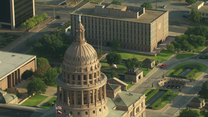 Reverse view of the Texas State Capitol dome, reveal John Reagan State Office Building, Downtown Austin, Texas Aerial Stock Footage | AF0001_000145