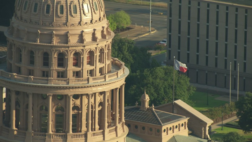 The Texas State Capitol dome and Texas flag in Downtown Austin, Texas Aerial Stock Footage | AF0001_000146
