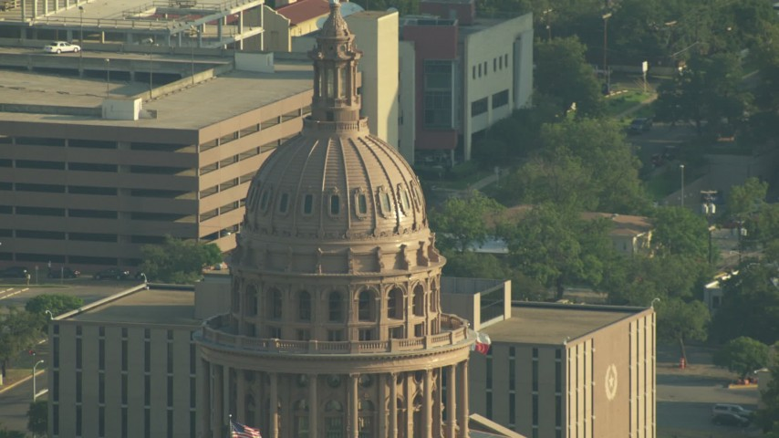HD stock footage aerial video tilt down Texas State Capitol Dome to reveal American and Texan flags, Downtown Austin, Texas Aerial Stock Footage | AF0001_000147