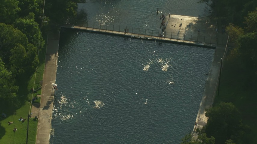 Orbit people swimming in a canal in Austin, Texas Aerial Stock Footage   AF0001_000153