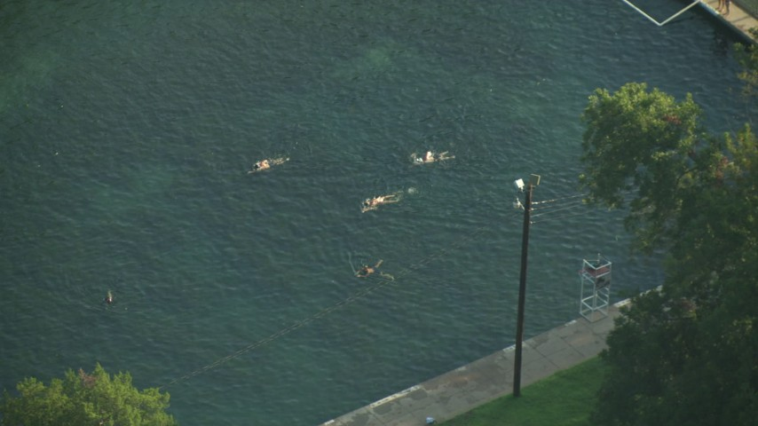 Reverse view of people swimming in a canal, Austin, Texas Aerial Stock Footage | AF0001_000154