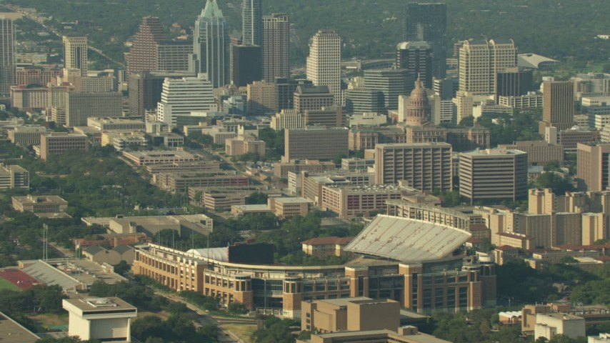 Fly over Texas Memorial Stadium to approach Downtown Austin, Texas Aerial Stock Footage | AF0001_000157