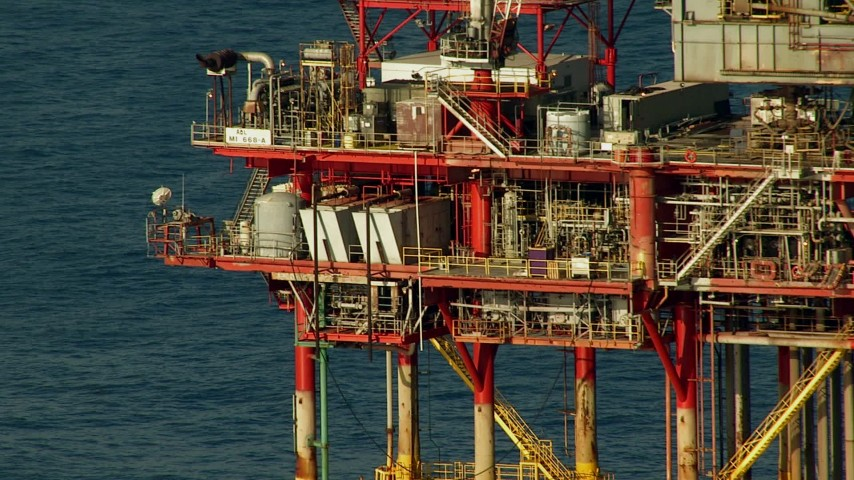 Tilt up the side of an oil rig in the Gulf of Mexico Aerial Stock Footage | AF0001_000182