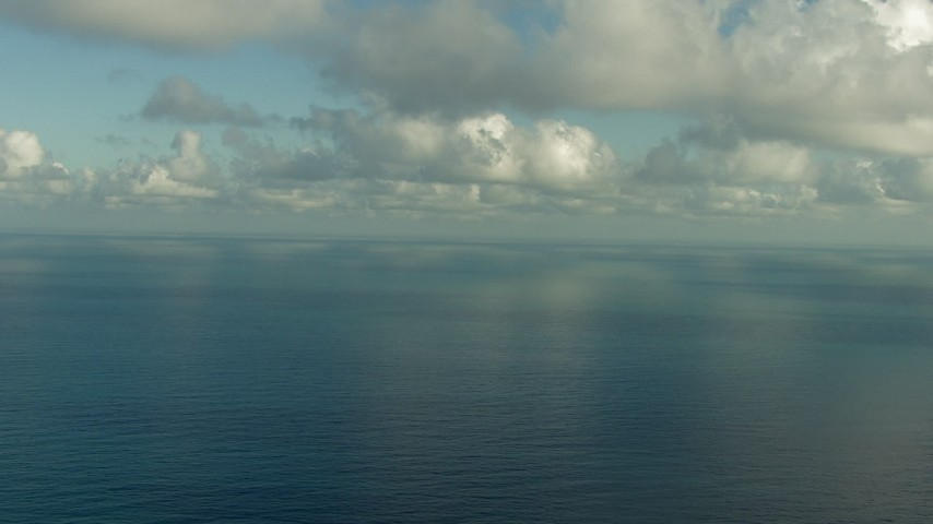 Fly over the Gulf of Mexico and beneath clouds, and pan across the water Aerial Stock Footage | AF0001_000186